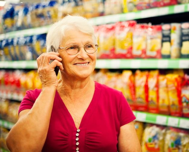 Starszy kobieta rozmawia przez telefon w supermarkecie