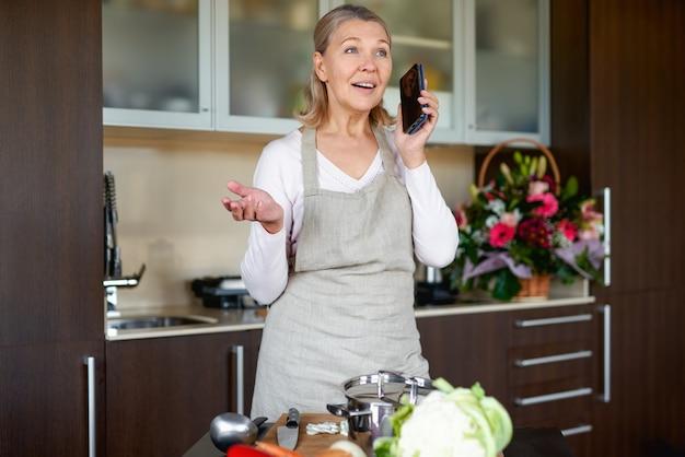 Starszy kobieta rozmawia telefon w kuchni i przygotowuje jedzenie