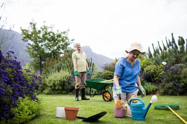 Starszy kobieta sadzenie kwiatów, podczas gdy starszy mężczyzna stoi z taczką w tle