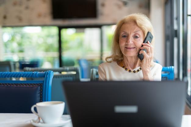 Starszy kobieta siedzi i za pomocą komputera przenośnego i telefonu komórkowego