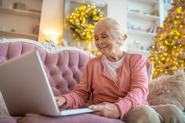 Starszy kobieta siedzi na kanapie i po czacie wideo