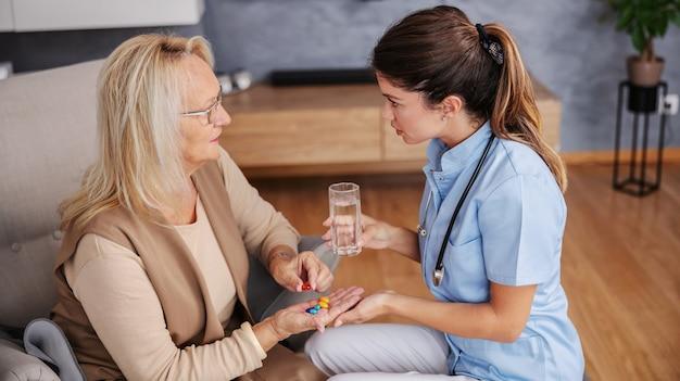 Starszy kobieta siedzi w domu i trzymając rękę pełną pigułek i słuchanie porad pielęgniarki.