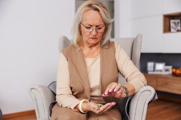 Starszy kobieta siedzi w domu w fotelu i trzymając rękę pełną pigułek i witamin