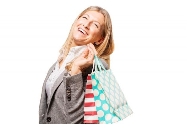 Starszy kobieta śmieje się z torby na zakupy