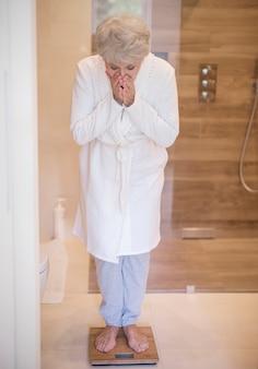 Starszy kobieta stojąca na wadze