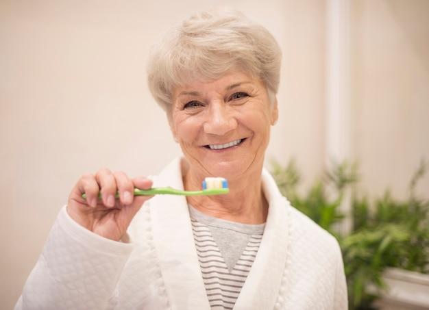 Starszy kobieta szczotkuje zęby