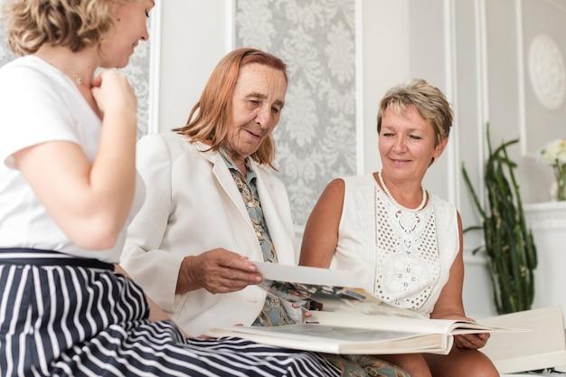 Starszy kobieta szuka albumu fotograficznego z córką grand córki