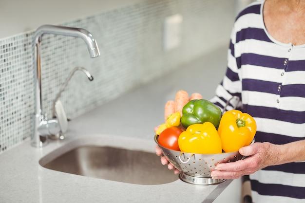 Starszy kobieta trzyma durszlak z warzywami