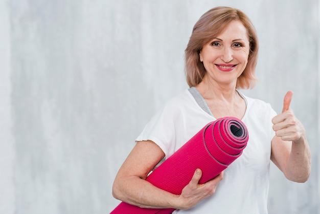 Starszy kobieta trzyma matę do jogi pokazując gest thumbup na szarym tle