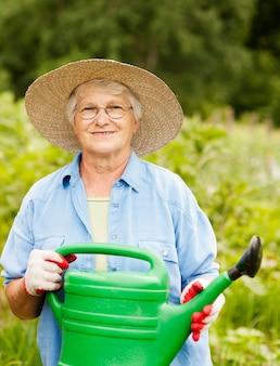 Starszy kobieta trzymając konewka