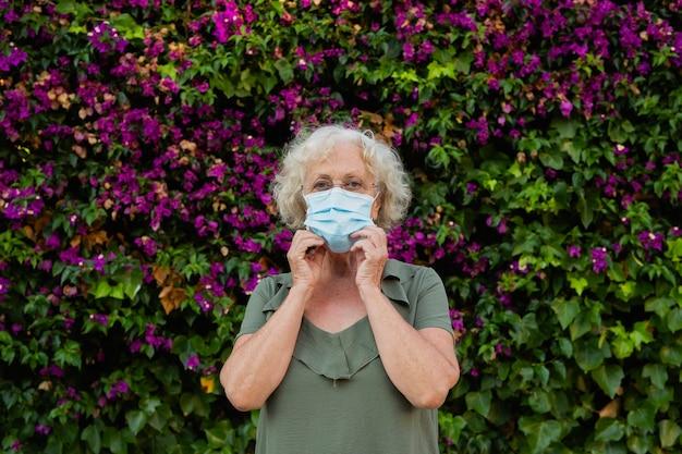 Starszy kobieta ubrana w niebieską maskę chirurgiczną na ulicy