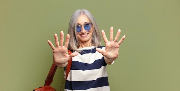 Starszy kobieta uśmiecha się i wygląda przyjaźnie, pokazując numer dziesięć lub dziesiątą ręką do przodu, odliczając w dół