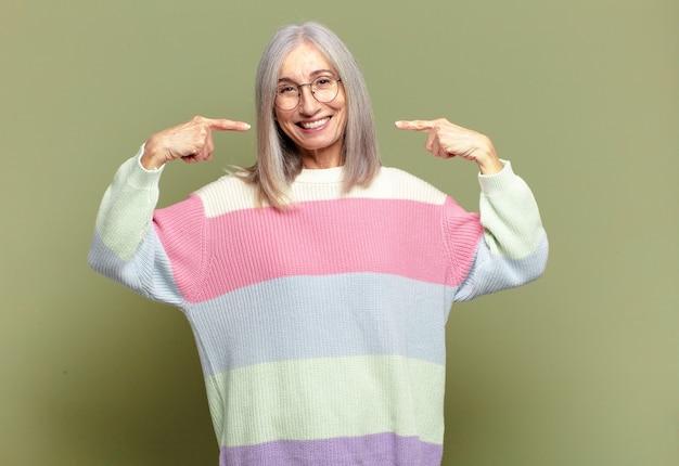 Starszy kobieta uśmiecha się pewnie, wskazując na swój szeroki uśmiech, pozytywne, zrelaksowane, zadowolone nastawienie