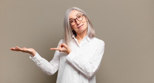 Starszy kobieta uśmiecha się radośnie i wskazuje na kopiowanie miejsca na dłoni z boku, pokazując lub reklamując obiekt