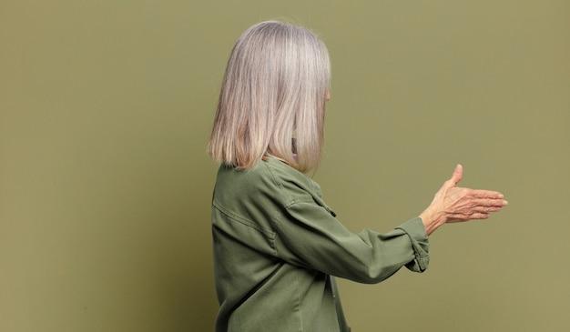 Starszy kobieta uśmiecha się, wita i oferuje uścisk dłoni, aby zamknąć udaną transakcję, koncepcja współpracy