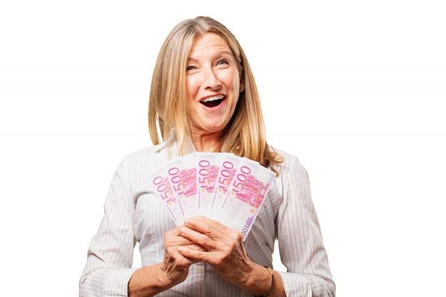 Starszy kobieta uśmiecha się z bonów w ręku