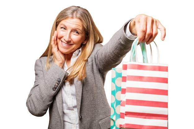 Starszy kobieta uśmiecha się z torby na zakupy