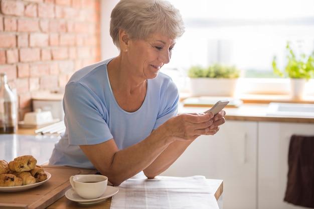 Starszy kobieta używa swojego telefonu komórkowego