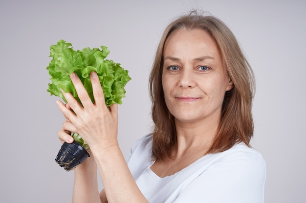 Starszy kobieta w białej koszuli trzyma kilka zielonej sałatki