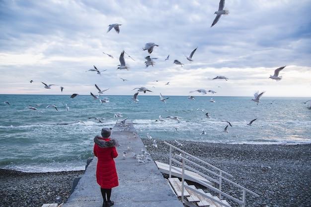 Starszy kobieta w czerwonej kurtce mewy paszy na morzu