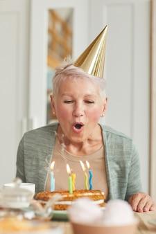 Starszy kobieta w kapeluszu siedzi przy stole i dmuchanie świeczki na jej tort urodzinowy