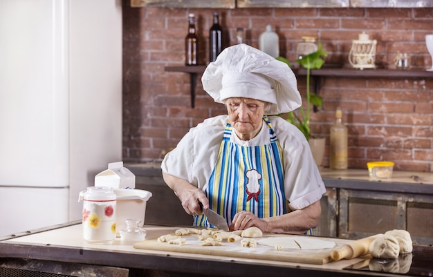 Starszy kobieta w kapeluszu szefa kuchni przygotowywanie ciastek w kuchni w domu