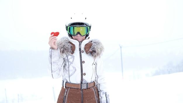 Starszy kobieta w kasku i okularach z snowboard stoi w górach zimą z miękkim sercem. walentynki. wysokiej jakości zdjęcie