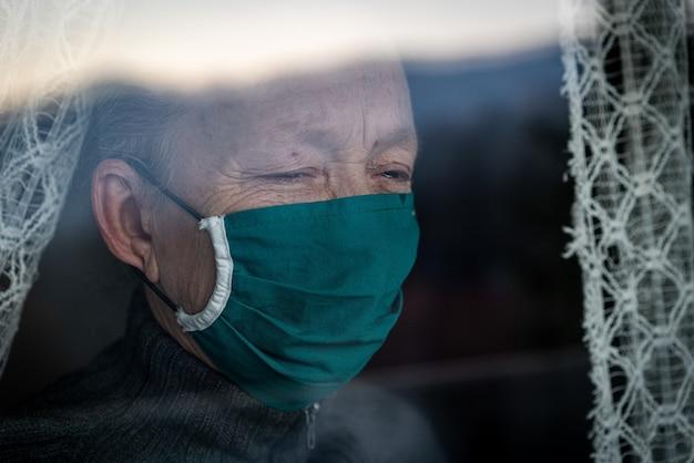 Starszy kobieta w kwarantannie płacze na oknie