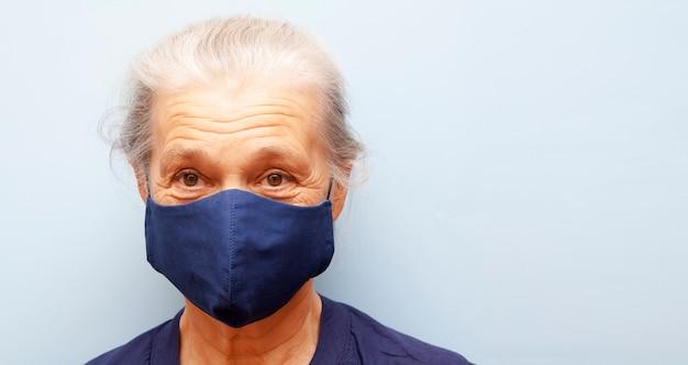 Starszy kobieta w masce szmatką na niebieskim tle. baner z miejsca na kopię