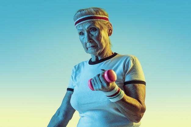 Starszy kobieta w treningu sportowego z ciężarami na tle gradientu, światło neonowe. modelka w świetnej formie pozostaje aktywna. pojęcie sportu, aktywności, ruchu, dobrego samopoczucia, pewności siebie. copyspace.