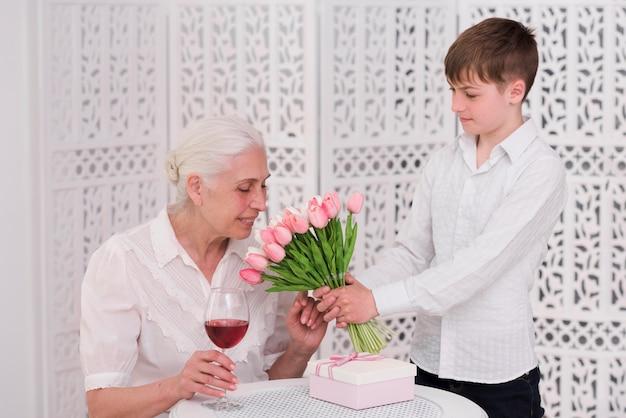 Starszy kobieta wącha kwiaty tulipanów podane przez jej wnuka