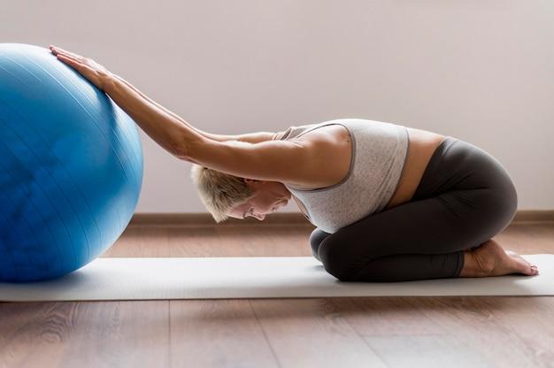 Starszy kobieta z krótkimi włosami robi ćwiczenia rozciągające