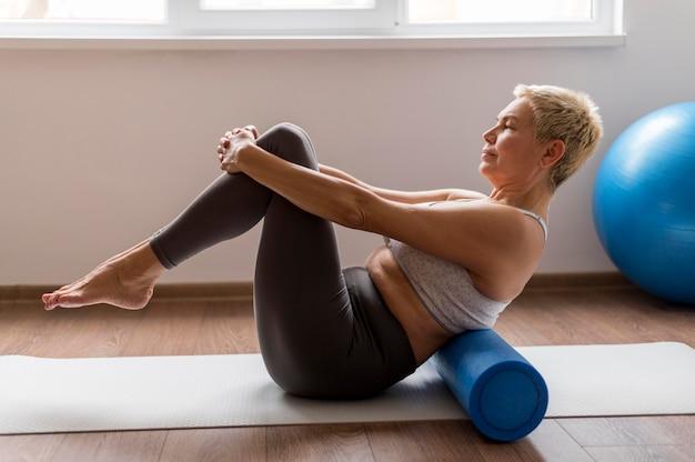Starszy kobieta z krótkimi włosami za pomocą maty do jogi
