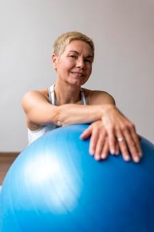 Starszy kobieta z krótkimi włosami za pomocą piłki fitness