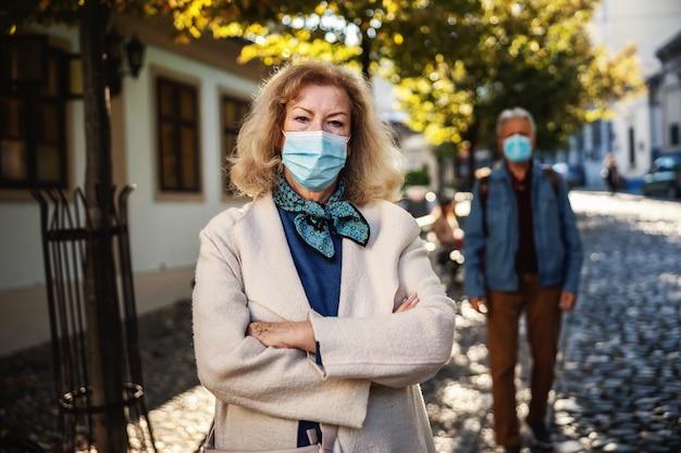 Starszy kobieta z maską ochronną na stojąco z rękami skrzyżowanymi w starej części miasta.