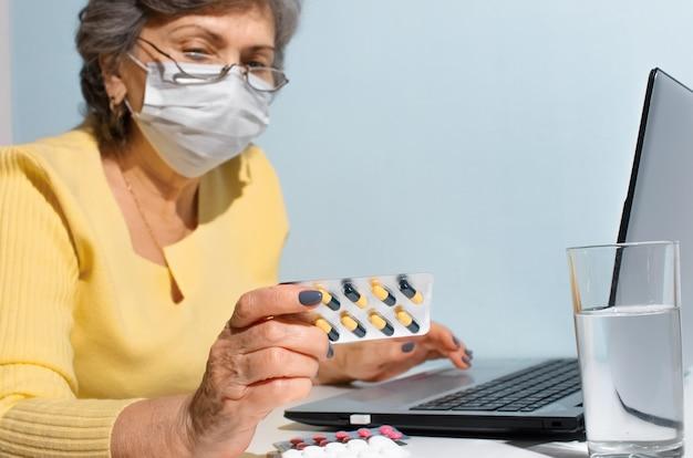 Starszy kobieta z okularami i maską medyczną instrukcje czytania medycyny, selektywne focus. starsza kobieta używa laptopa w domu. koncepcja konsultacji online z lekarzem, nowy normalny.