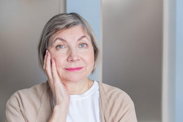 Starszy kobieta z siwymi włosami uśmiecha się patrząc w kamerę przed ręką w twarz