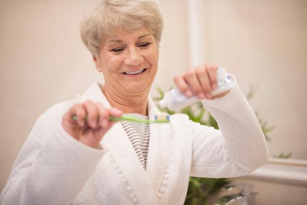 Starszy kobieta za pomocą jej szczoteczki do zębów