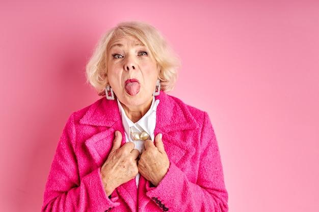 Starszy kobieta zabawy w czasie wolnym, pokazując język w aparacie, szalona kobieta w różowym stylowym płaszczu na białym tle na różowej przestrzeni