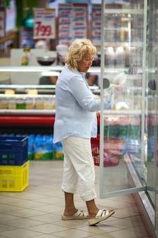 Starszy kobieta zakupy na produkty mleczne