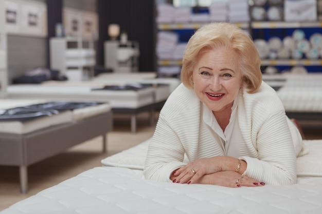 Starszy kobieta zakupy przy sklepem meblowym