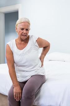 Starszy kobiety cierpienie od bólu pleców podczas gdy siedzący w sypialni