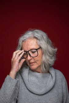 Starszy kobiety kładzenia eyeglasses na jej twarzy przeciw barwionemu tłu