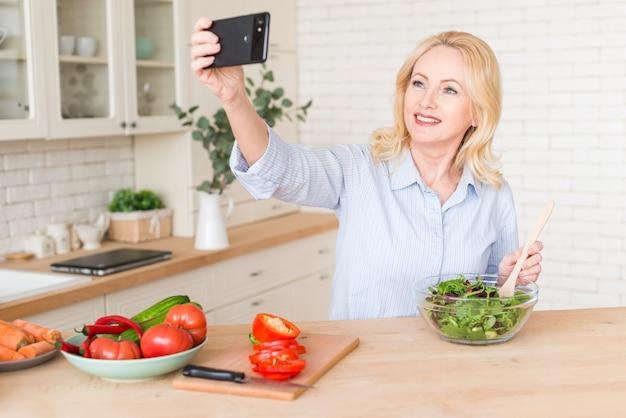 Starszy kobiety narządzania sałatka bierze selfie na telefonie komórkowym