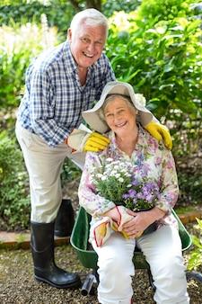 Starszy kobiety obsiadanie w taczce mężem w ogródzie