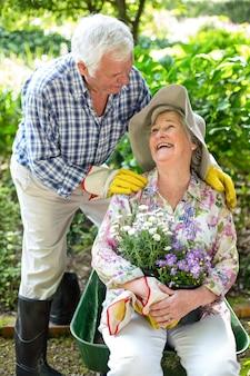 Starszy kobiety obsiadanie w taczce podczas gdy patrzejący męża w ogródzie