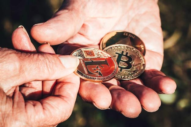 Starszy kobiety ręka trzyma cryptocurrency monetę w ostrości daje starszemu mężczyzna ręce