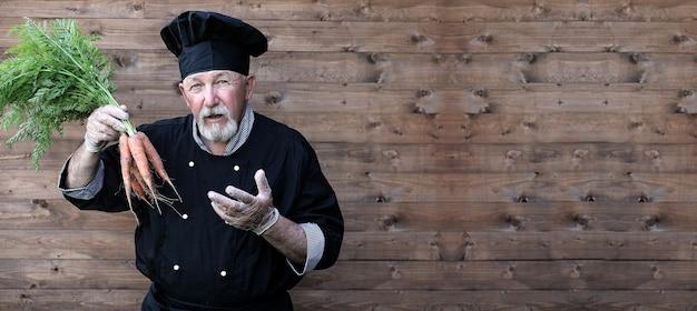 Starszy kucharz w mundurze z warzywami w dłoniach
