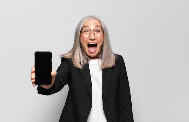 Starszy ładna bizneswoman z inteligentnym telefonem.