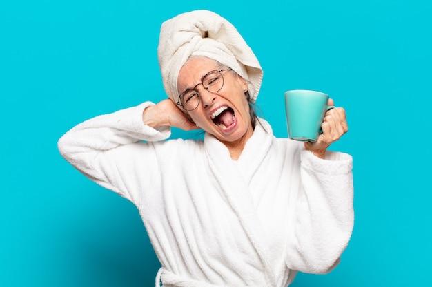 Starszy ładna kobieta ma na sobie szlafrok i kawę